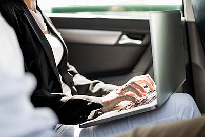 Midsection of businesswoman using laptop in taxi - p426m844660f by Maskot