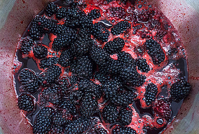 Blackberries simmering in large saucepan, overhead close up - p429m2023245 by Seb Oliver
