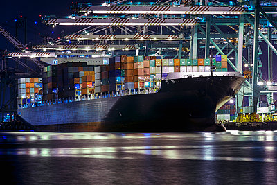 A cargo ship loaded with freight and the shipping yard illuminated at night - p442m883819 by Mike Raabe