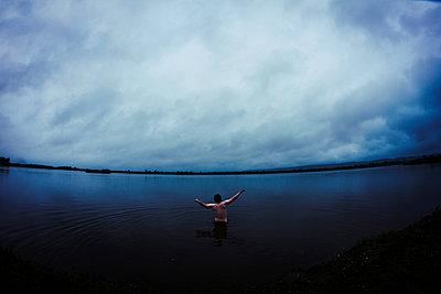 Caucasian man standing in still remote lake - p555m1410920 by Maxim Chuvashov