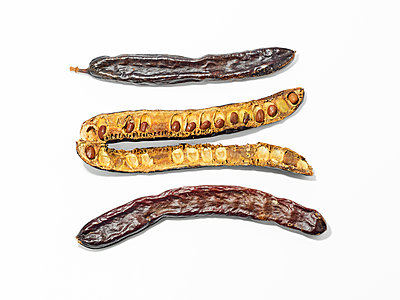 Carob beans against white background - p885m2200464 by Oliver Brenneisen