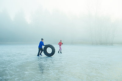 Man rolling tyre on frozen lake - p924m1230154 by Pete Saloutos