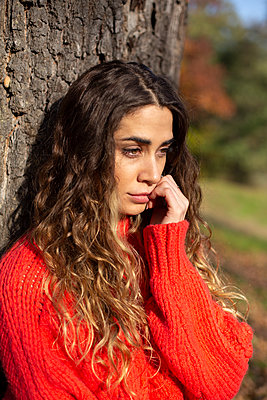 Young woman in red jumper leaning against tree - p975m2222099 by Hayden Verry