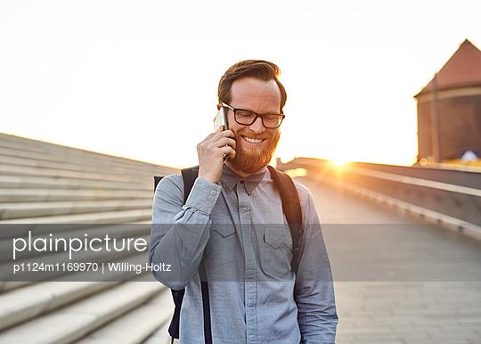 Mann telefoniert im Gegenlicht - p1124m1169970 von Willing-Holtz