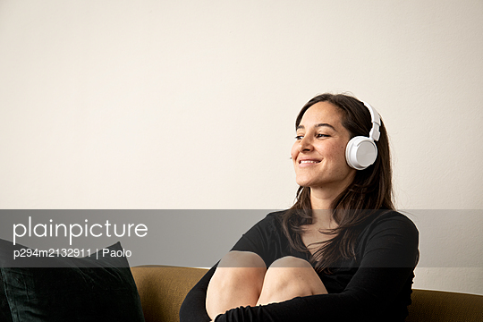 Brunette woman listens to music through headphones  - p294m2132911 by Paolo