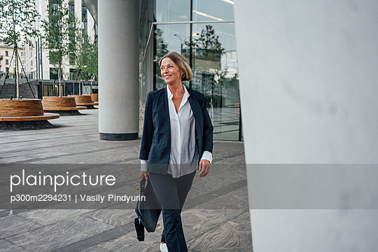 Smiling female professional with bag looking away while walking on walkway - p300m2294231 by Vasily Pindyurin