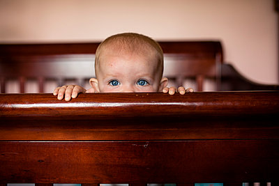 Portrait of baby girl peeking over crib - p1166m1474360 by Cavan Images
