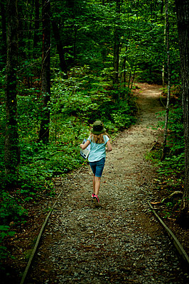 Rear view of girl running on footpath amidst trees at forest - p1166m1568889 by Cavan Images