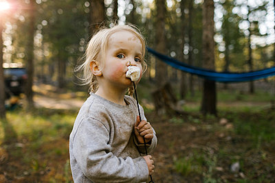 Portrait of girl (2-3) eating marshmallow in forest, Wasatch Cache National Forest - p1427m2213548 by Jessica Peterson
