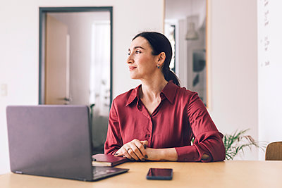 Smiling businesswoman with laptop looking away while sitting at table in home office - p300m2266624 by Katharina Mikhrin