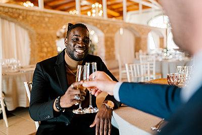 Elegant men sitting and toasting champagne at banquet - p300m2274268 by Ezequiel Giménez