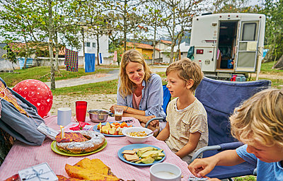 Family at picnic table celebrating boys birthday, Florianopolis, Santa Catarina, Brazil, South America - p429m1519605 by Stephen Lux