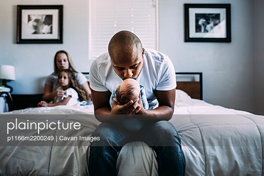 Center portrait of dad kissing newborn baby on bed - p1166m2200249 by Cavan Images