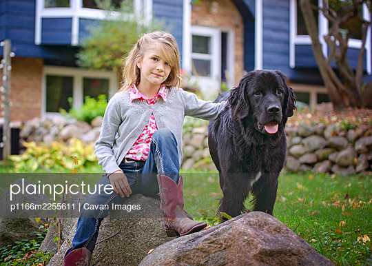 Young Blond Girl Sitting Outside on a Rock with Big Black Dog - p1166m2255611 by Cavan Images