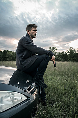 Man sits on hood holding a pistol - p1019m1424629 by Stephen Carroll