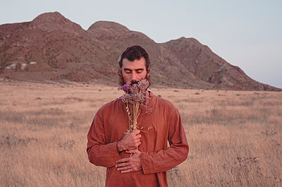 bearded man standing in the middle of the desert smelling a bouquet of flowers held on his chest - p1656m2248584 by Javier Martinez Bravo