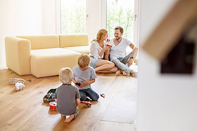 Happy family with two sons in living room of their new home - p300m2121765 by Peter Scholl