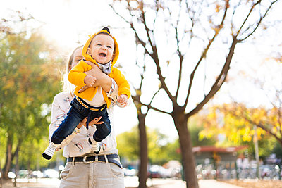 Happy mother playing with baby boy in a park - p300m2154773 by Eloisa Ramos
