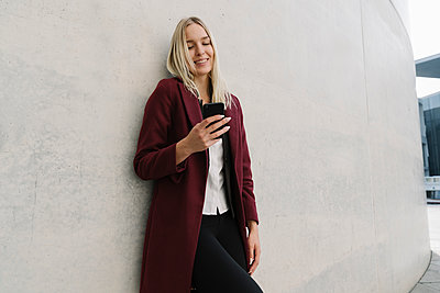 Blond businesswoman using smartphone and leaning on a wall - p300m2155140 by Hernandez and Sorokina