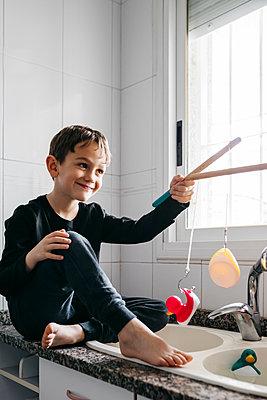 Portrait of happy boy fishing rubber ducks in kitchen sink - p300m2189106 by Josep Rovirosa