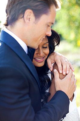 Newlywed couple embracing outdoors - p312m1076150f by Juliana Wiklund