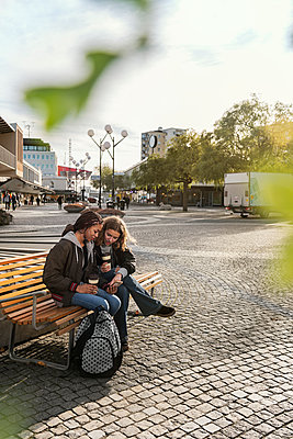 Teenage girls using smart phone on bench - p352m2121180 by Folio Images