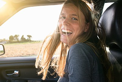 Portrait of happy young woman in car with long blond windswept hair - p429m1080002f by Philipp Nemenz