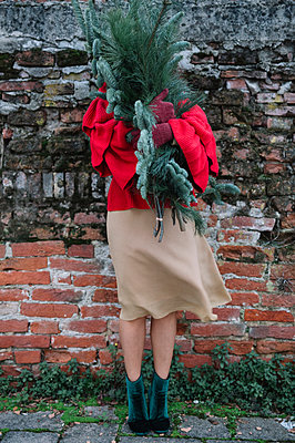 Young woman in front of old brick wall holding christmas tree - p429m2052375 by Alberto Bogo