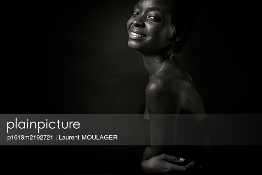 Portrait of a young woman smiling at the the camera - p1619m2192721 by Laurent MOULAGER