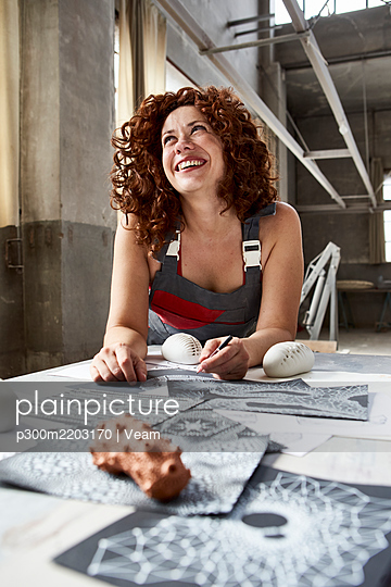 Smiling female stonemason with sketches on table looking up in workshop - p300m2203170 by Veam