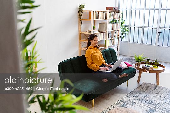 Young woman using laptop while sitting on sofa at home - p300m2251469 by Giorgio Fochesato