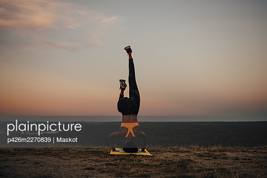 Young female athlete practicing yoga during sunset - p426m2270839 by Maskot