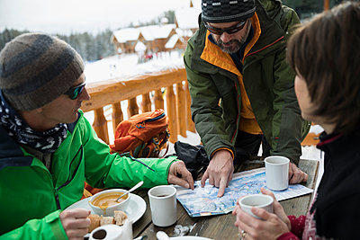 Mature friend skiers enjoying breakfast, preparing with map on ski resort balcony - p1192m1546508 by Hero Images