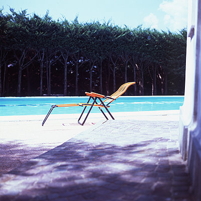 Empty deck chair by the poolside - p1462m1516133 by Massimo Giovannini
