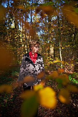 Woman walking through forest - p227m1503292 by Uwe Nölke