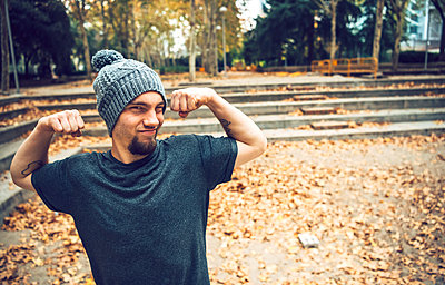 Man flexing muscles while standing in park during autumn - p300m2206681 by klublu