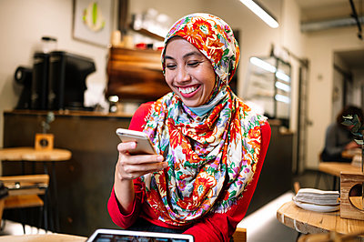 Mid adult woman in hijab smiling while looking at mobile phone - p300m2240873 by Jose Luis CARRASCOSA