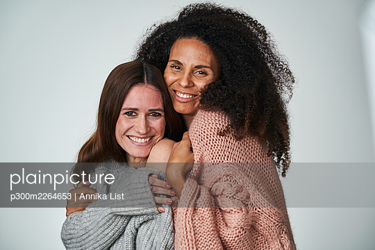Happy female friends embracing on gray background - p300m2264653 by Annika List