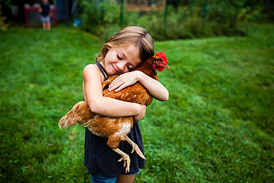 Smiling girl with eyes closed holding hen while standing in yard - p1166m1183027 by Cavan Images