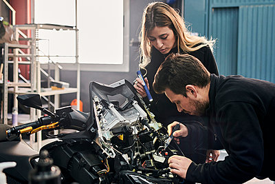 A woman and a man are working together in a mechanic shop - p1166m2268336 by Cavan Images