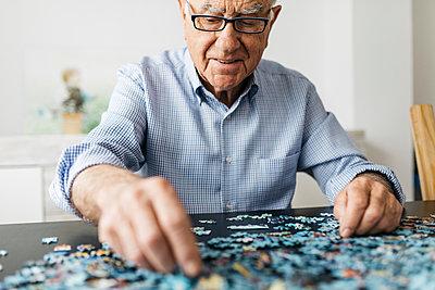 Senior man doing a jigsaw - p300m2005561 von Josep Rovirosa