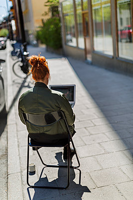 Woman using laptop outdoors - p312m2140037 by Pernille Tofte