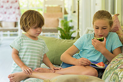 Caucasian brother and sister watching digital tablet on sofa - p555m1522775 by Marc Romanelli