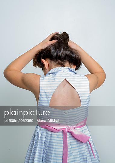 Mädchen spielt mit ihrem langen Haar - p1508m2082350 von Mona Alikhah