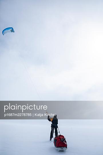 Man snowkiting while pulling a ski sled (toboggan) - p1687m2278785 by Katja Kircher