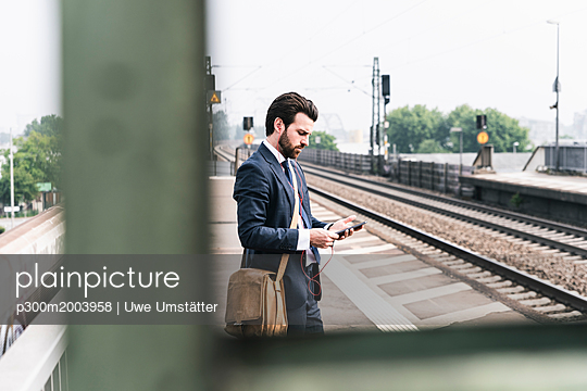 Businessman with cell phone and earphones waiting at the platform - p300m2003958 von Uwe Umstätter