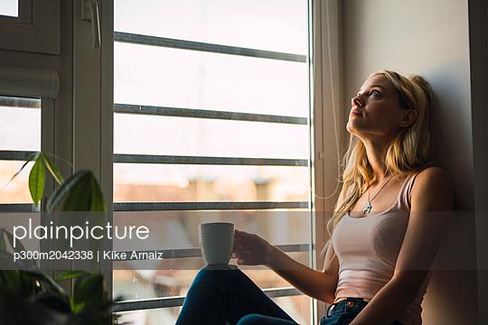 Blond young woman holding coffee mug sitting in windowsill - p300m2042338 von Kike Arnaiz