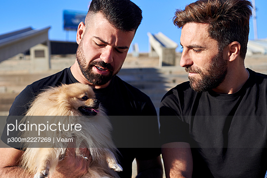 Gay couple with dog spending leisure time during weekend - p300m2227269 by Veam