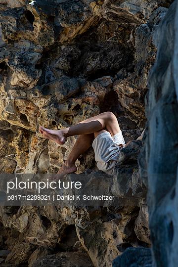 Mann hiding behind rocks, Beihai Park, Peking - p817m2289321 by Daniel K Schweitzer