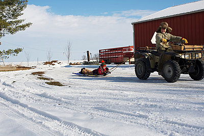 grandpa pulling child on sled  - p1169m1032693 by Tytia Habing
